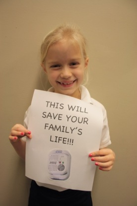 Samantha's sister with a photo of a carbon monoxide detector.